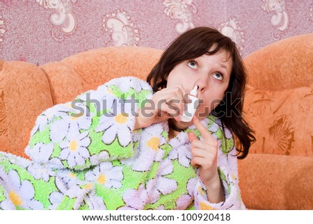 a simple girl dripping spray in the nose lying on the couch