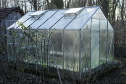 A simple glass greenhouse in a vegetable garden.