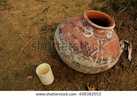 A simple handmade earthen pot used for water sits in a field during a hot day.