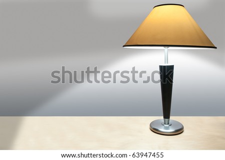 A simple lamp with yellow shade on a wooden desk casting a shadow onto a plain wall.
