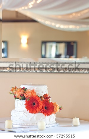 A simple three tier white wedding cake highlighted with orange flowers, a mirror above highlighting the ceiling decorations of the venue.
