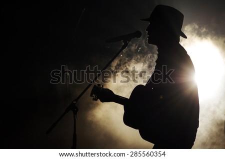 A singer man silhouette playing guitar