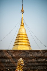 A Singh sculpture in front of tile roof and golden pagoda at traditional temple in Northern Thailand.