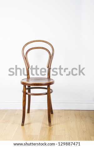 A single antique wooden chair, on a polished pine floor against white wall