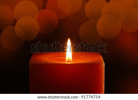 A single burning red candle