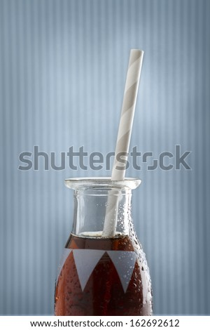 A single cola soda pop retro bottle and straw on blue background