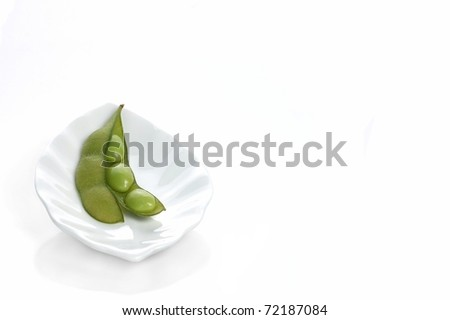 A Single Edamame Soybean Pod, Open to Expose the Soybeans inside, Sitting on a White Plate, With room for Text