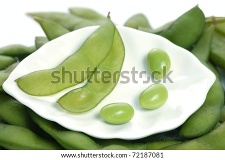 A Single, Empty Edamame Soybean Pod with Three Individual Soybeans on a White Plate Sitting on a Bed of Soybean Pods