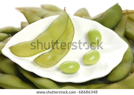 A Single, Empty Soy Bean Pod with Three Individual Soy Beans on a White Plate Sitting on a Bed of Soy Bean Pods