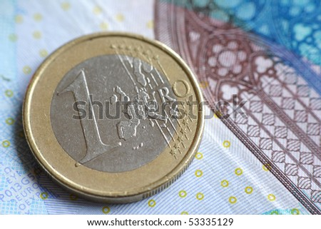 A single euro coin on a banknote.