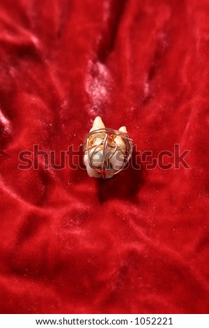 a single extracted human tooth wrapped in copper wire on red velvet, as part of a Voodoo Spell