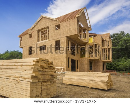 A single family home under construction. The house has been framed and covered in plywood