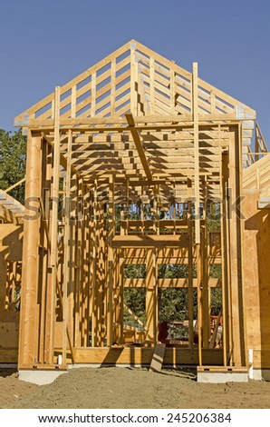 A single family home under construction. The house has been framed and covered in plywood and roof trusses in place.