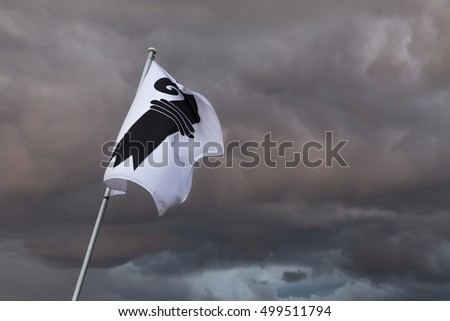 A single flag of Basel in Switzerland in front of a gloomy sky. Dark storm clouds loom in the background #499511794