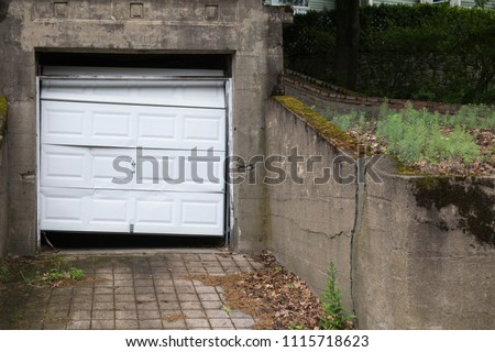 A single garage door hangs askew and dented in a property that appears, dirty, neglected and covered in old leaves