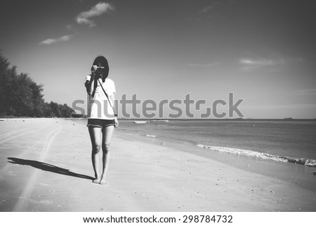 A single girl take a picture at the beach (black and white)