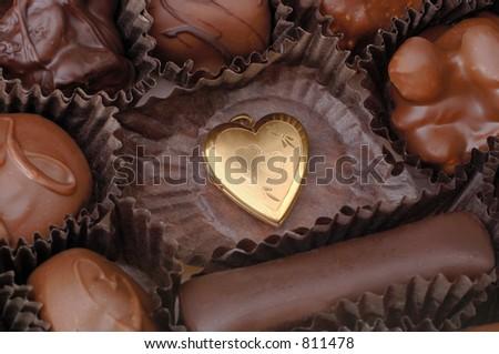 A single gold heart among handmade chocolates. Focus = the gold heart. 12MP camera, macro.