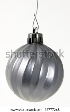 A single isolated silver Christmas bauble hanging. (focus on middle of bauble) - stock photo