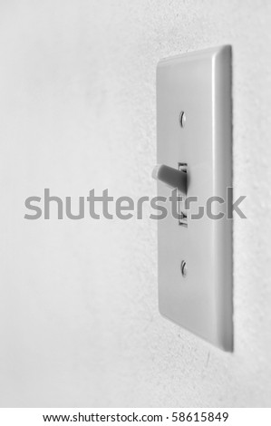 A single light switch on a white wall at an angle.