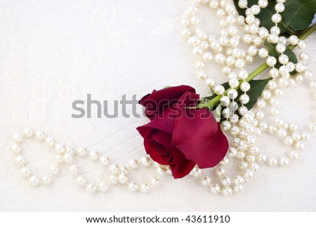 A single long stemmed red rose with a string of off-white pearls on a textured off-white background, great for Valentine's Day