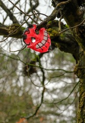 A single macabre, grinning Halloween mask hangs from the trees in this local park.