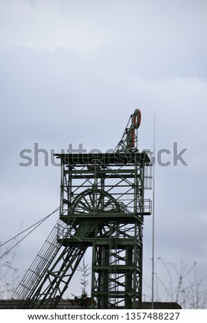 A single mine shaft lift stands against a grey sky #1357488227