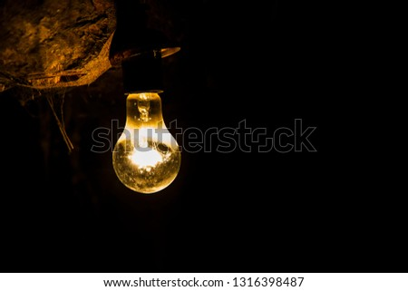 A single old-style incandescent bulb, shining with a golden yellow glowing light in a dark room. Photo in landscape orientation and the object on the left side.