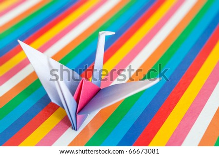 A single paper bird on a colorful stripes background. Shallow depth of field.
