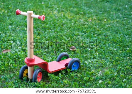 A single push-scooter for children in a garden.