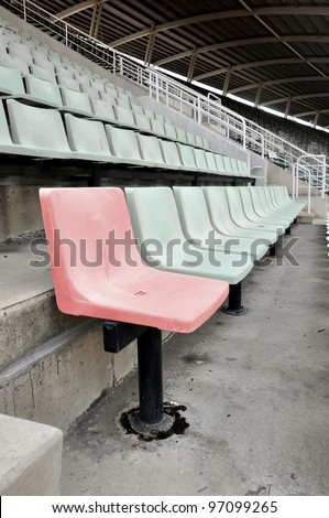 A single red chair in a multitude of white chair