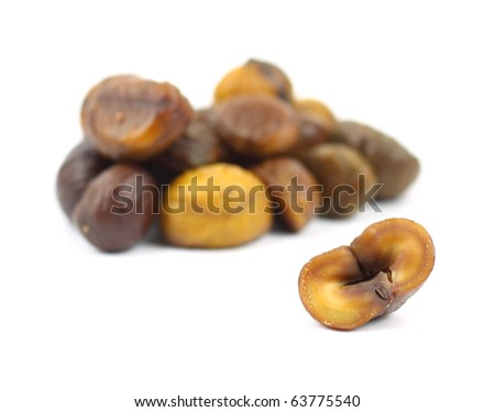 A single roasted chestnut that has been cut in half in the foreground with several roasted chestnuts in the background.