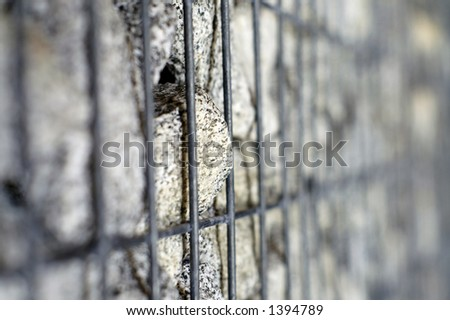 A single rock in a steelcage tries to break out; very shallow DOF with focus on tip of stone