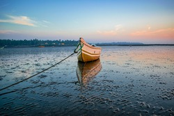 A single rowing fishing boat docked tied with anchor rope on beach in low tide abstract sunset background image with beautiful reflection on water,abstract sunset background on beach with color shades