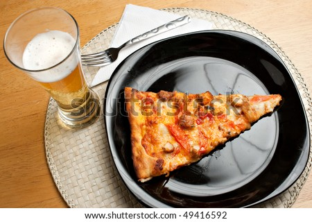 A single slice of buffalo chicken pizza and a glass of golden lager beer.  The perfect weekend take out dinner.