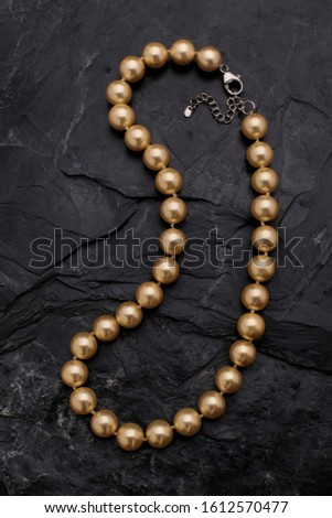 A single strand golden color pearl necklace lies on a rough black slate background.
