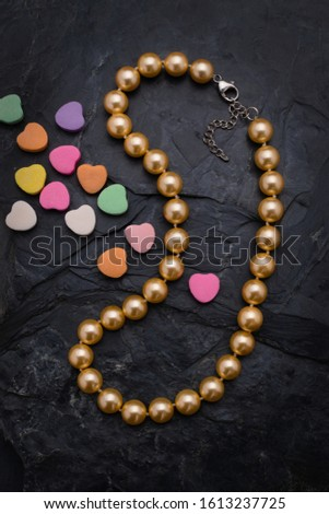 A single strand golden color pearl necklace lies on a rough black slate background. For Valentines Day the necklace is accented by small colorful candy hearts.