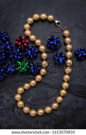 A single strand golden color pearl necklace lies on a rough black slate background. The necklace is accented by small metallic bows.