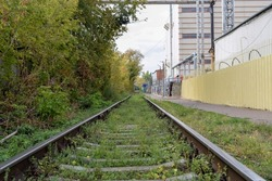A single-track railway leading through the forest and industrial enterprises on a summer day