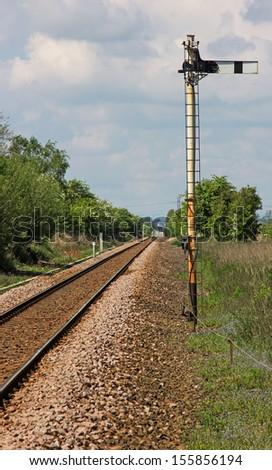 A single track railway line showing the reverse of a Home semaphore signal, the line in the distance is shimmering in the summer heat