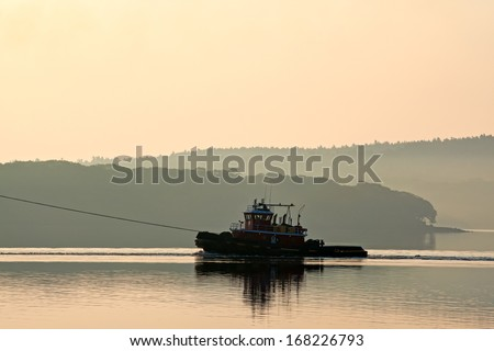 A single tugboat on the Penobscot river in the early morning light.