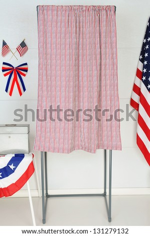 A single voting booth with American flags and bunting with a table and ballot box.