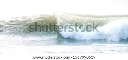 A single wave crashing on the shore. Bright, light edit to elicit a feeling of calmness.