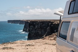 A single white campervan parked on top of the limestone Bunda Cliffs along the coast of the Nullabor Plains, overlooking the bright blue ocean below