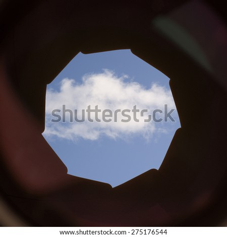 A single white cloud on a blue sky seen through the lens and aperture of a camera. Conceptual image of view on cloud computing, digital communication and storage.