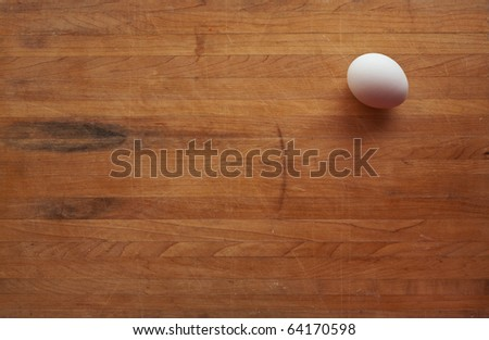 A single white egg sits on a butcher block counter with area suitable for text