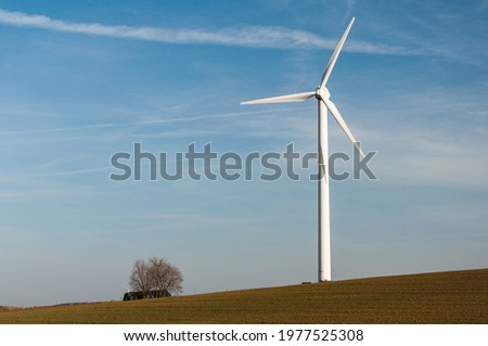 A single wind generator isolated in an agricultural field with a tree under a blue sky Stock photo ©