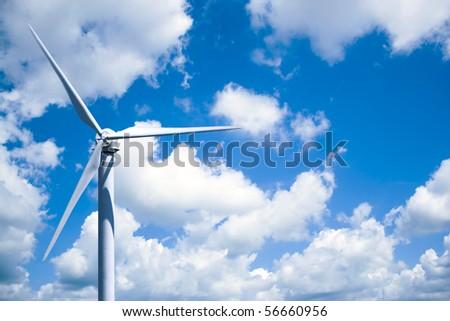 A single wind turbine over a cloud filled blue sky.