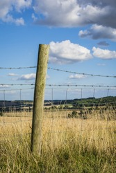 A single wooden fence post and barbed wire fence in the English countryside on a sunny day.