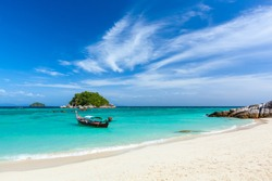 A single wooden fishing boat mooring by the clean sandy beach of Ko Lipe Island on a clear blue sky sunny day