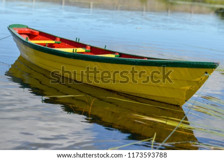 A single yellow wooden dory with a red interior and green trim floats in water. The boat's reflections can be seen in the water along with strands of grass.